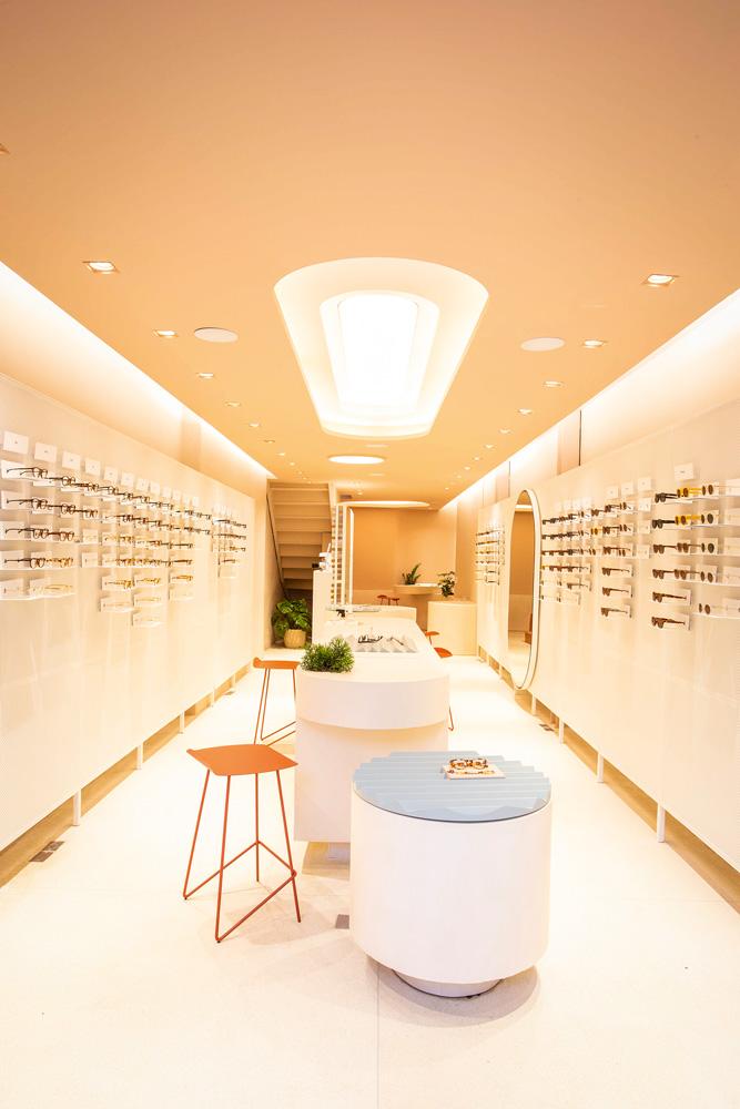 Uma loja de óculos. Paredes brancas com os modelos pendurados, alguns banquinhos e uma mesa no centro