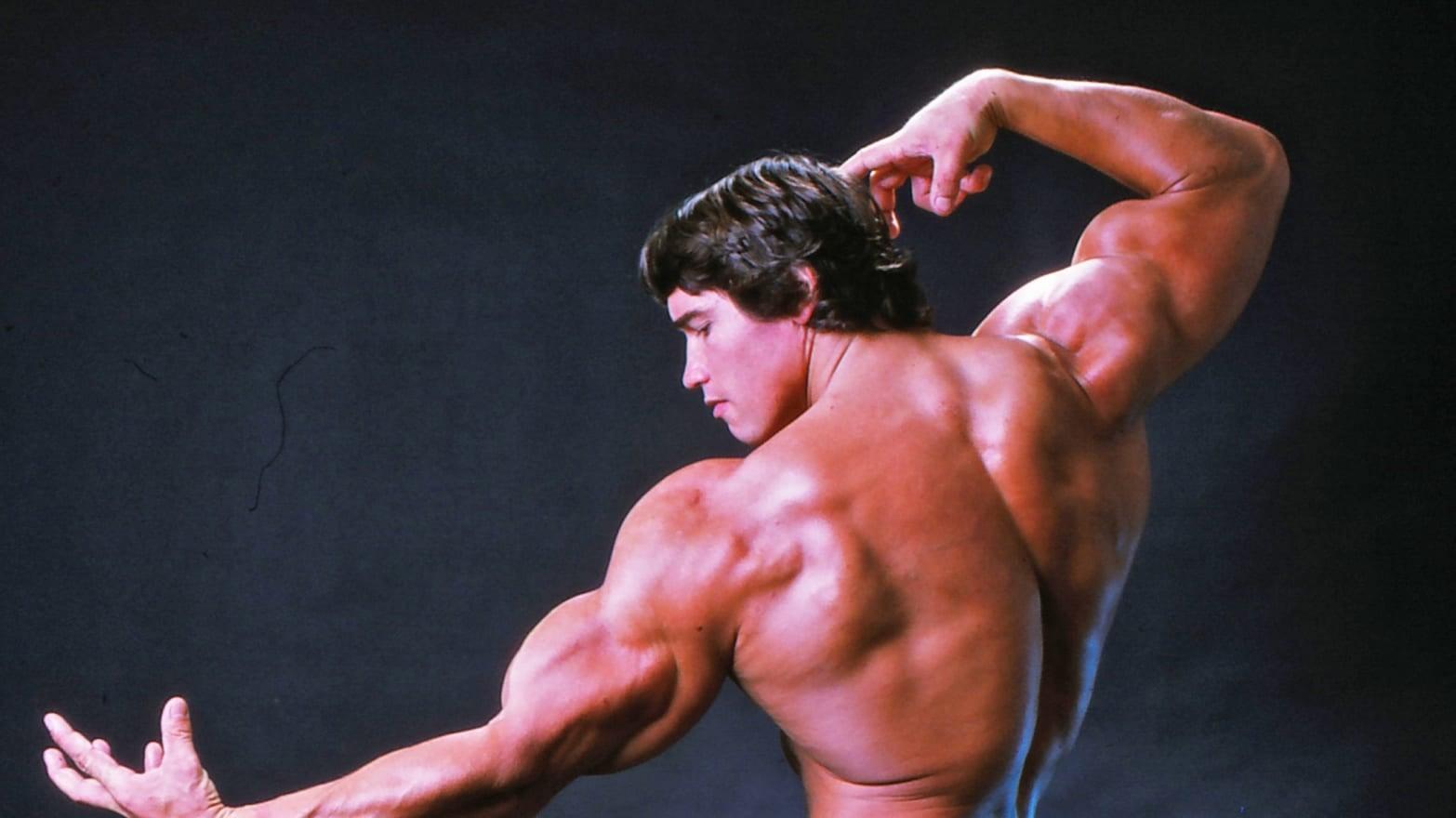 Arnold Schwarzenegger de costas fazendo pose com os músculos no filme