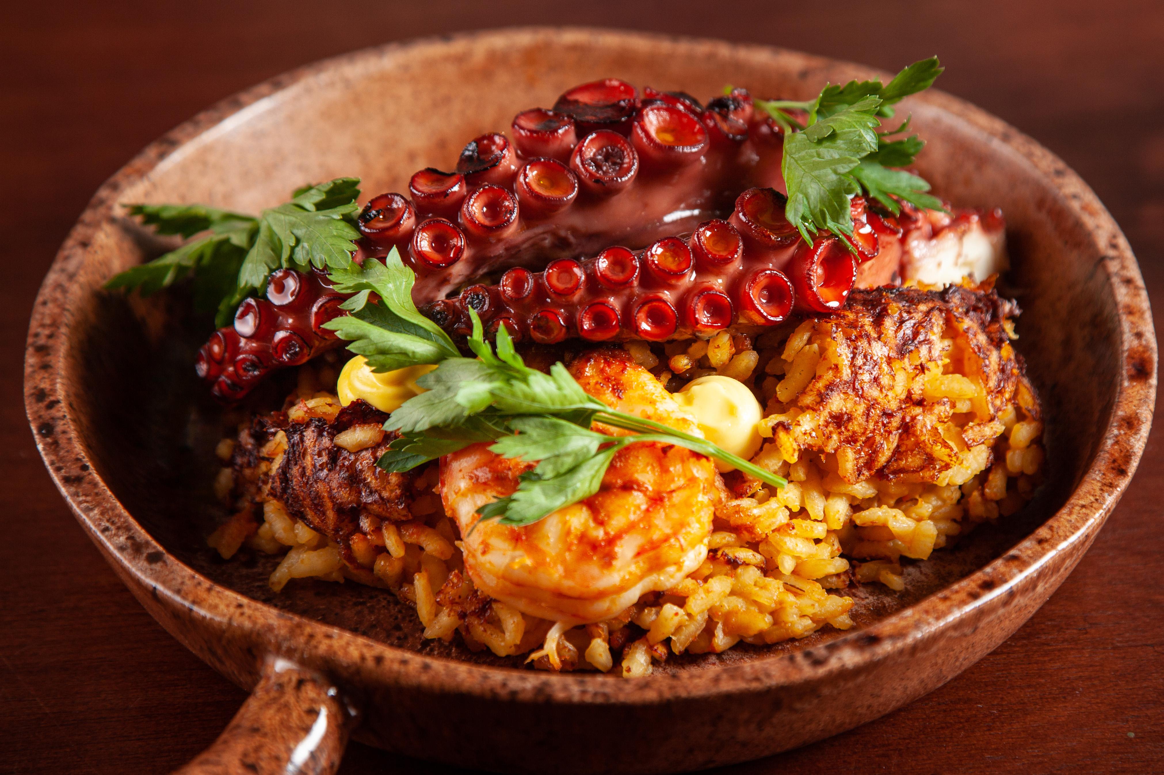 Em uma cumbuca funda e de cor marrom, é servido o prato junto de arroz, camarões e dois tentáculos de polvo