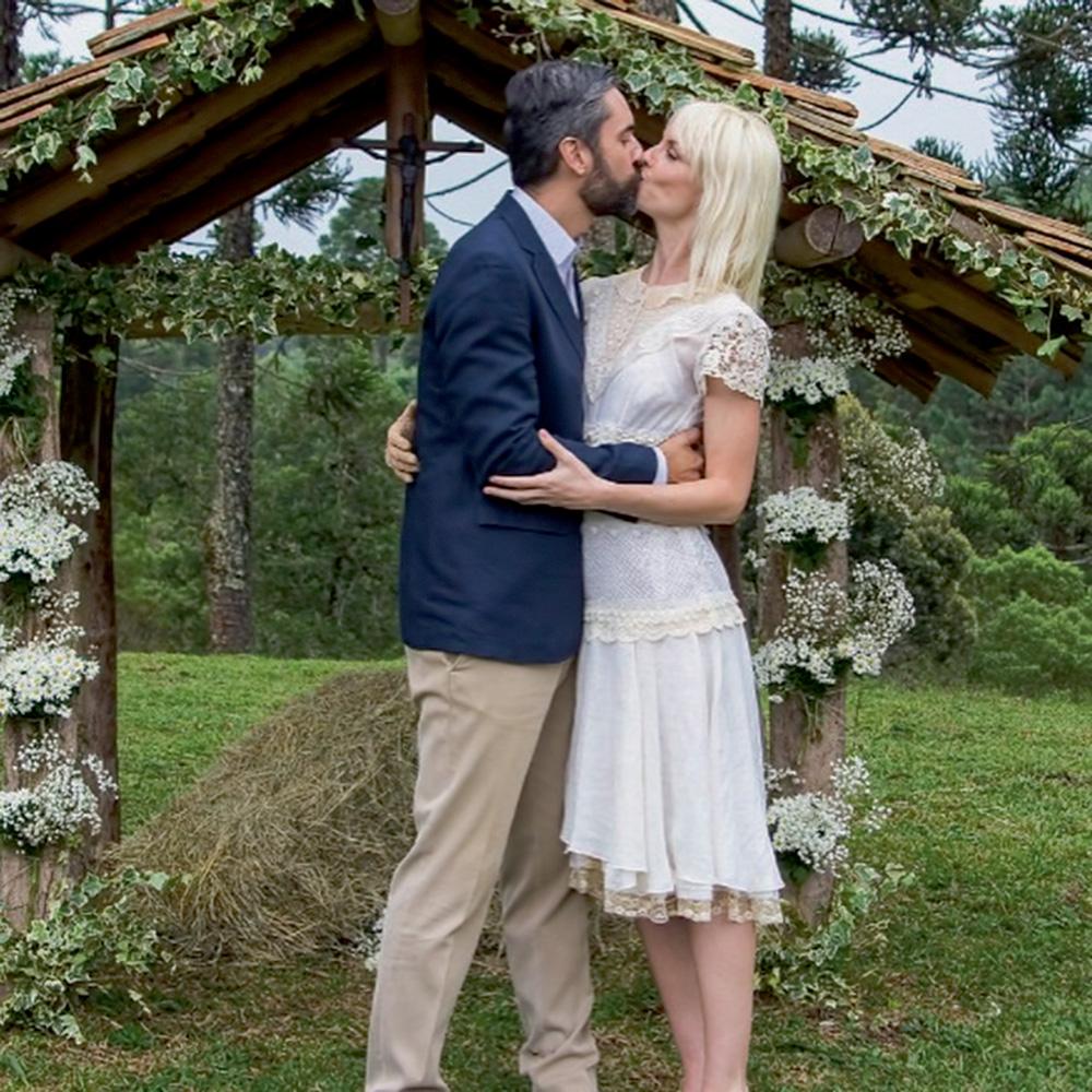 augusto e ana se beijando, ele com um terno, ela de vestido branco, em seu casamento, em um local aberto com gramado e diversas árvores. atrás deles há uma estrutura estilo portal de madeira ornada com flores