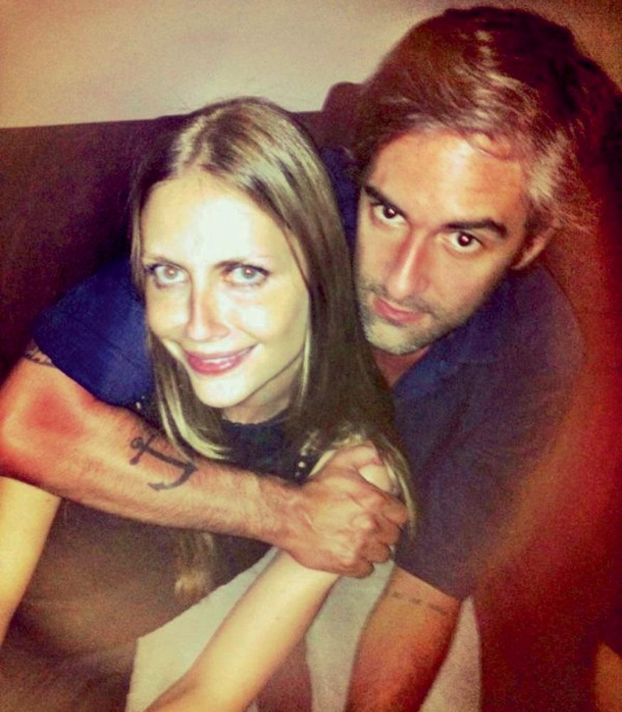foto de cima de augusto abraçando ana com seu braço envolvendo o pescoço dela. ela está sorrindo e ele está fazendo pose com expressão de sério