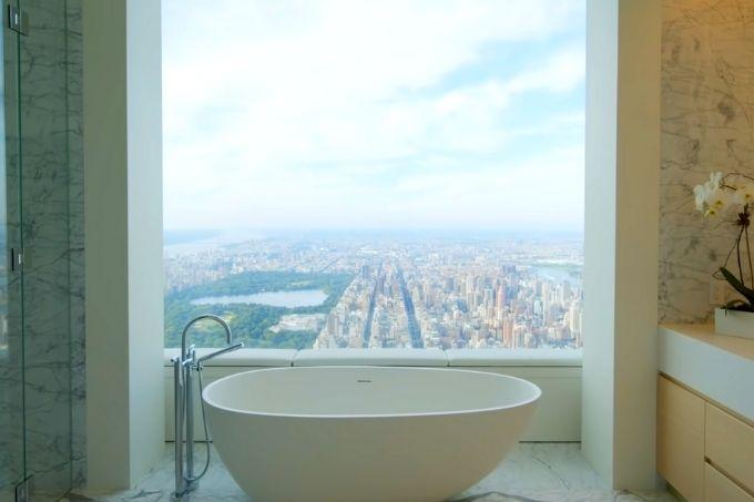 banheira no canto de banheiro de luxo com janela atrás com vista estonteante de nova york