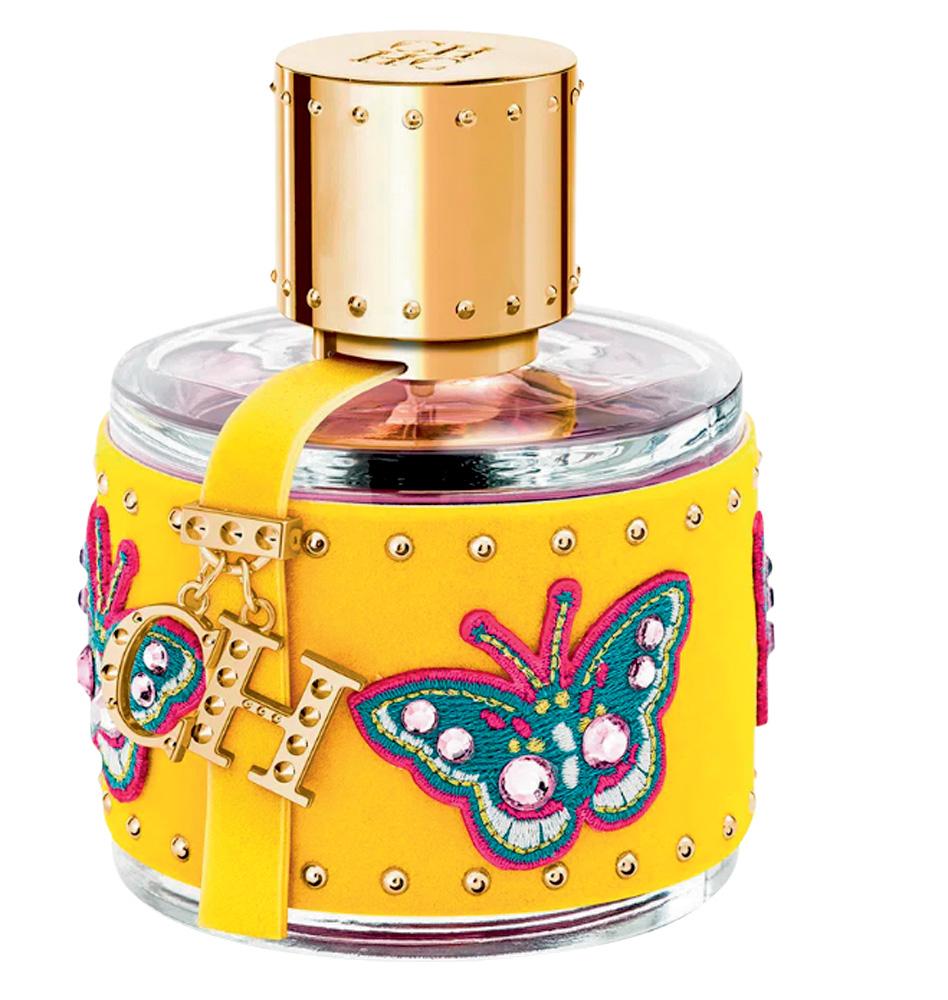 Frasco de perfume de vidro com uma capinha amarela e ilustrações em borboleta com strass e os pingentes das letras
