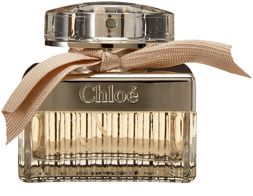 Frasco de perfume de vidro transparente com líquido bege, um laço bege e detalhes no frasco em bege e o escrito