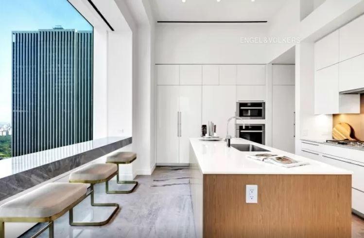 cozinha americana com um grande balcão grande ao centro, armários ao fundo e janela com balcão para sentar à esquerda
