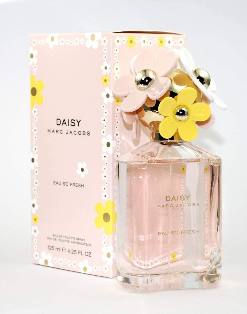 Frasco de perfume de vidro transparente e, ao lado, a caixa rosa. Tem detalhes de florzinhas neles