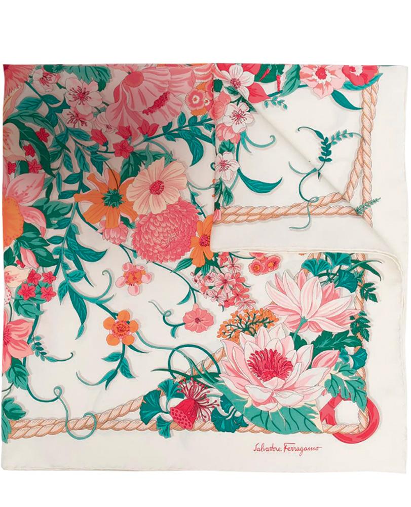 Um echarpe dobrado com estampa de ramos de folha verdes e flores rosa claro, pétalas e flores laranjas