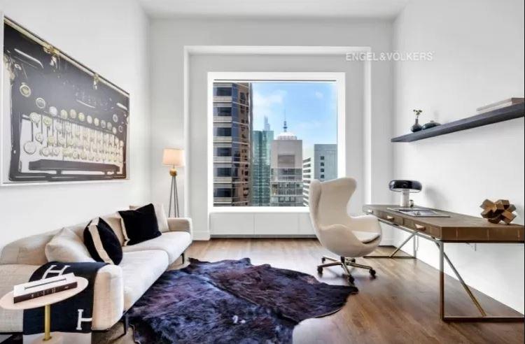 Escritório do apartamento de luxo do 432 Park Avenue, com janela grande, cadeira e escrivaninha de um lado e um sofá do outro