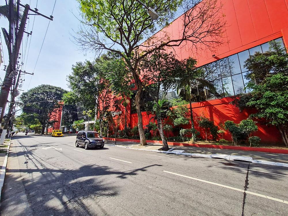 Foto mostra parte lateral do supermercado Extra, pintado todo de vermelho com janelas de vidro. Algumas árvores ao redor