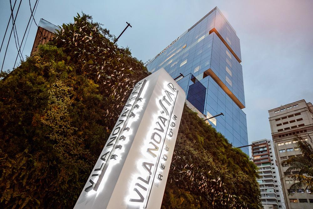 A imagem mostra a fachada do Vila Nova Star, com o nome do local em evidência e iluminado.
