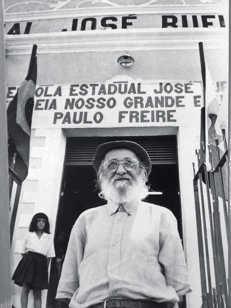 foto em preto e branco de paulo freire, que está olhando para o horizonte com barba longa branca e chapéu em frente a uma escola estadual que leva seu nome