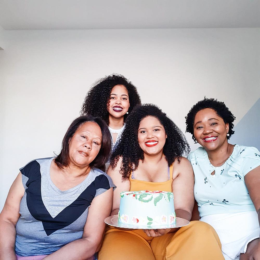 Quatro mulheres sorriem e olham para a câmera. A do centro segura um bolo