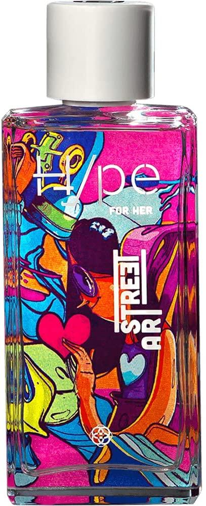 Frasco de perfume de vidro transparente e, ao fundo, uma arte super colorida como se fosse em grafite, dá para ver uma menina pintada