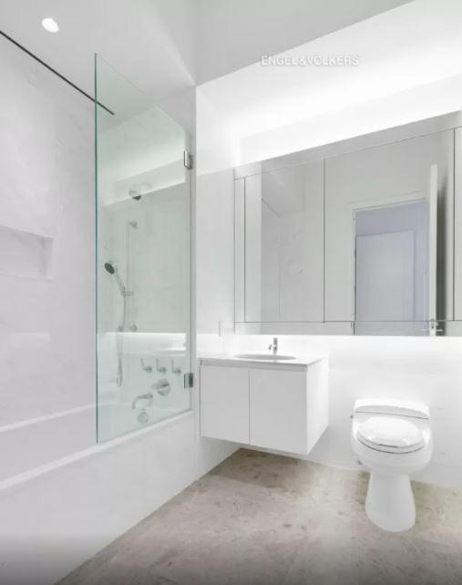 banheiro branco com vaso sanitário à direita, pia ao centro, espelho acima deles e box com vidro e ducha à esquerda