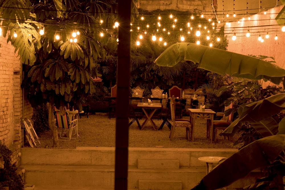 vista noturna, com luzes amarelas dispostas em fios suspensos, do jardim aberto do espaço, com grama, plantas, mesas e cadeiras