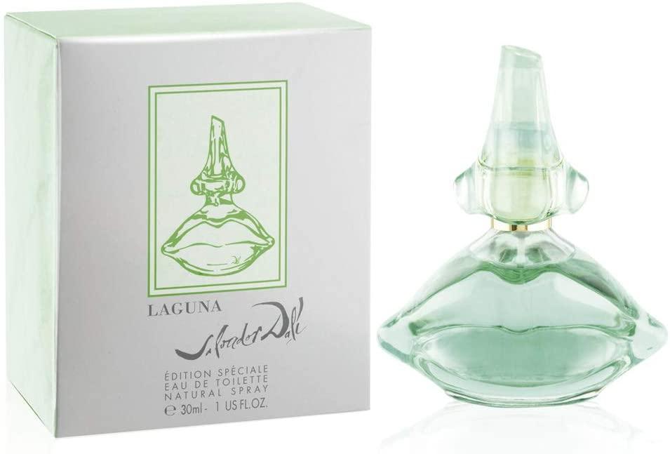 Frasco de perfume de vidro transparente verde e, ao lado, a caixa branca com detalhes em verde claro e o nome do item estampado