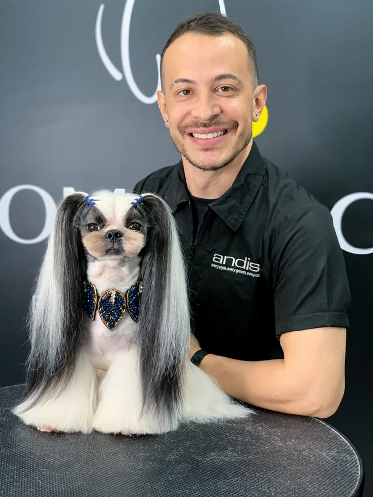 Luiz Renato segurando um cachorro que ele acabou de estilizar o pelo. o cachorro, em cima da mesa, tem mais pelo perto das extremidades das patas e o pelo das orelhas está grande
