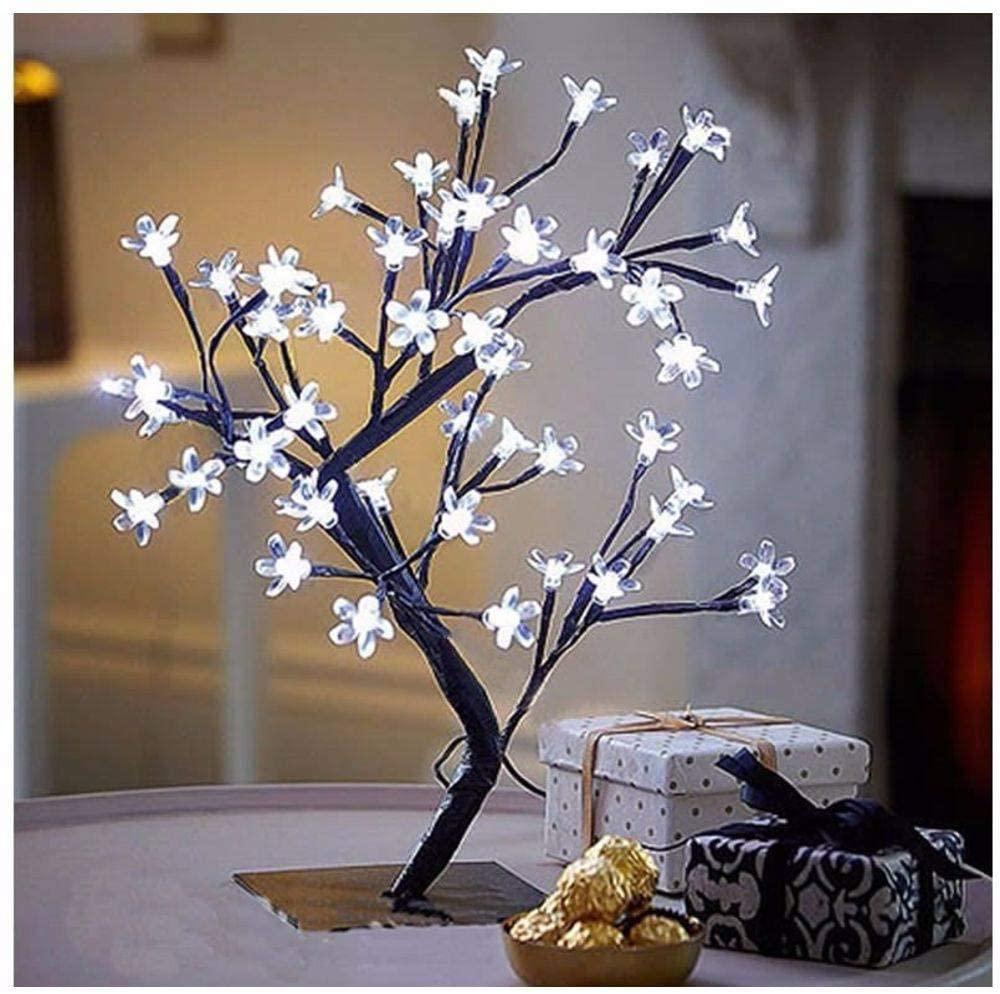 Uma luminária branca acesa em formato de árvore de cerejeira. Está em uma mesinha de canto ao lado de outros adornos