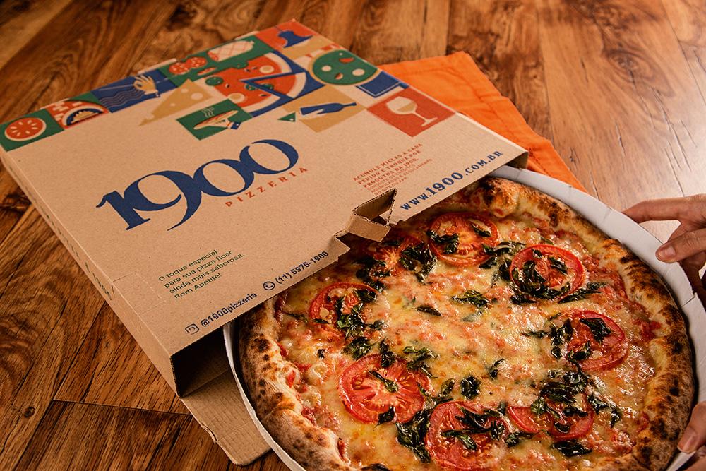 Pizza sabor margherita parcialmente dentro da caixa da pizzaria 1900