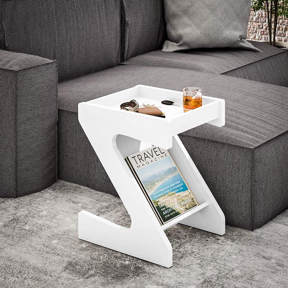 Do lado de um sofá cinza, um móvel de canto de mesa tem uma revista na parte de baixo e uma bebida e acessórios em cima