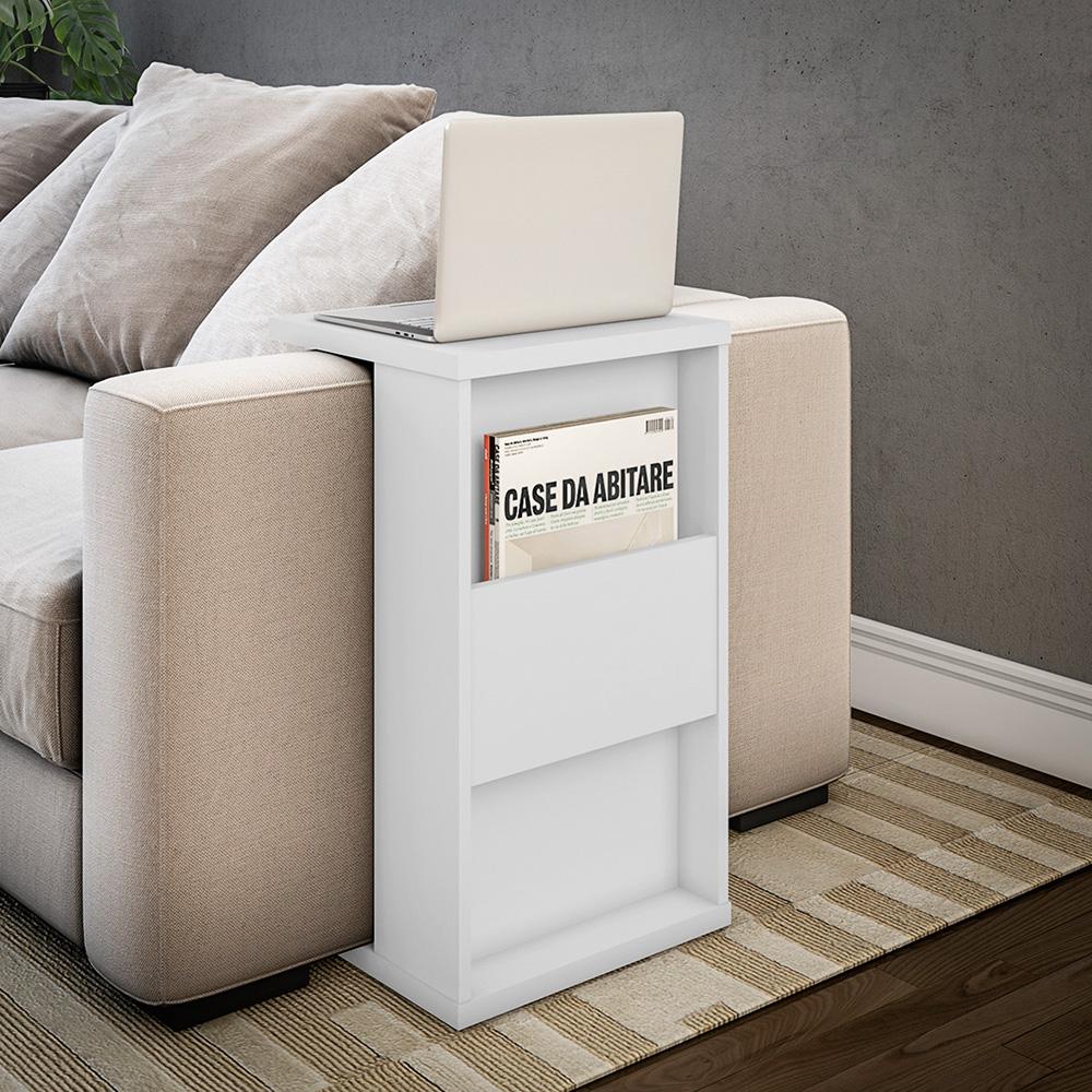Do lado de um sofá bege, um móvel de canto de mesa tem uma revista na parte de baixo e um notebook em cima