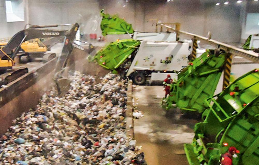 Uma estação de lixo. Caminhões jogam resíduos em um galpão