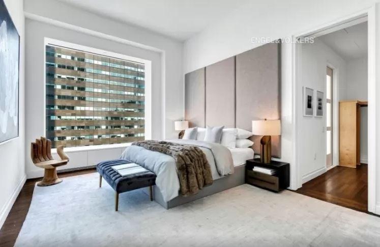 quarto com cama de casal, uma janela grande e muito espaço entre a cama e as paredes