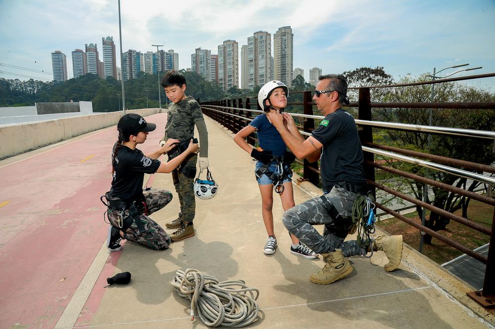 em ponte de sp com prédios ao fundo, dois instrutores colocam equipamentos de segurança em duas crianças, para que possam realizar rapel