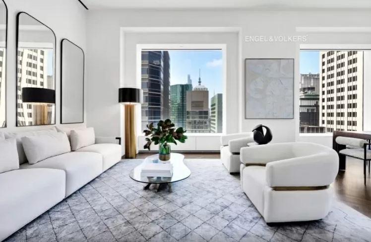 sala de estar ampla com diversos móveis claros e duas janelas grandes com vista para a cidade