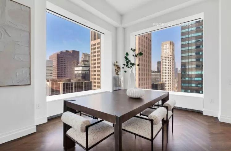 Sala de jantar com mesa e cadeiras e com duas janelas gigantes nas paredes