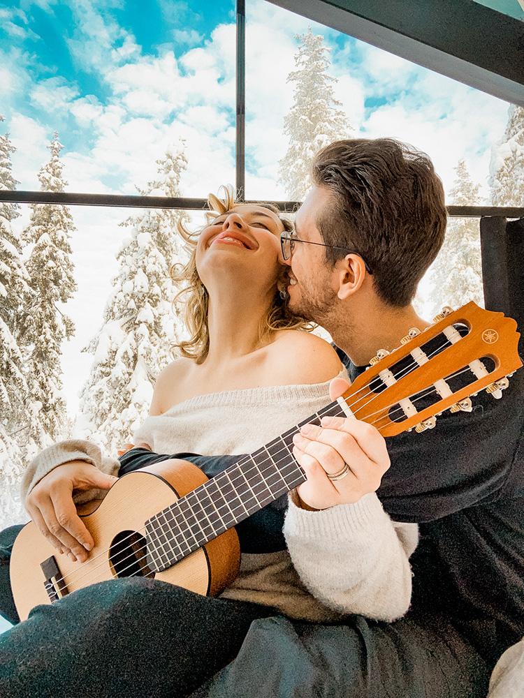 camila e carlos abraçados, com carlos por trás dela e dando um cheiro em seu pescoço e ela dando risada com o rosto para cima de olhos fechados. ela está segurando um violão e é possível ver que eles estão dentro de um ambiente que tem janelas para a vegetação com neve lá fora