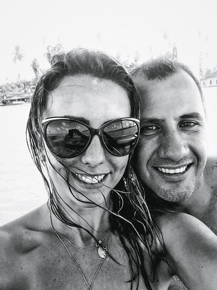 foto em preto e branco de ligia e roni abraçados e sorrindo em ubatuba. ligia está de óculos escuros