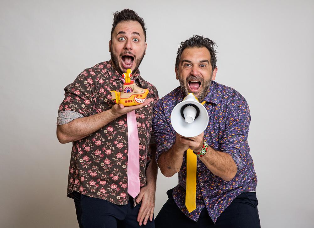 Dois homens vestem camisas floridas e posam para a foto com cara de surpresa. Um segura um submarino amarelo e o outro um megafone