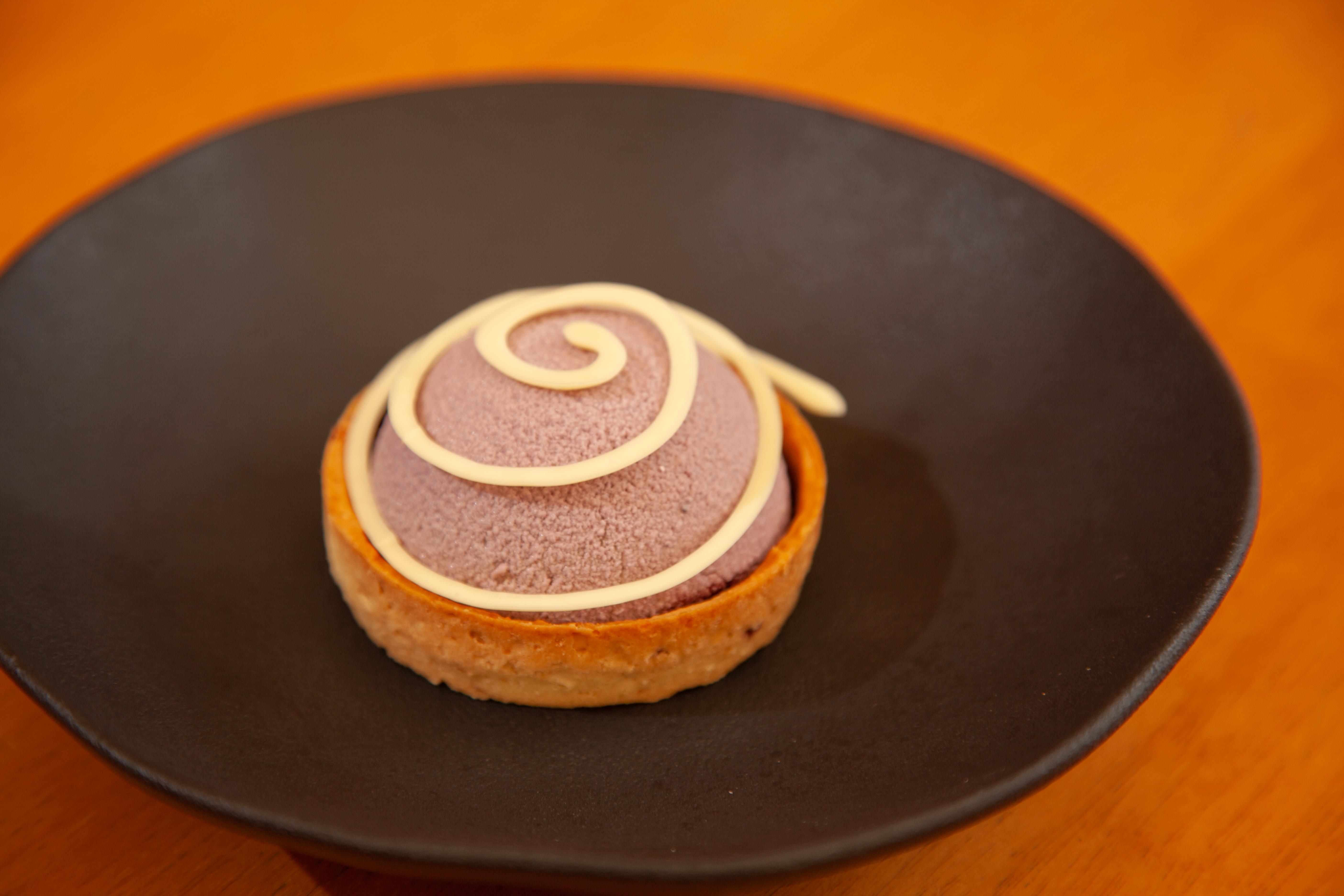Tortinha sucrée de amendoim vem com musse e geleia de açaí, paçoca e chocolate branco na decoração