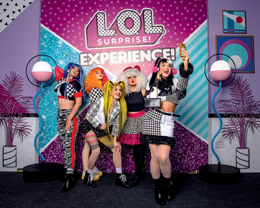 Em um cenário rosa, azul e roxo, cinco mulheres vestidas de bonecas L.O.L. posam para a foto. Elas vestem perucas e roupas chamativas e coloridas. Atrás, um banner escrito