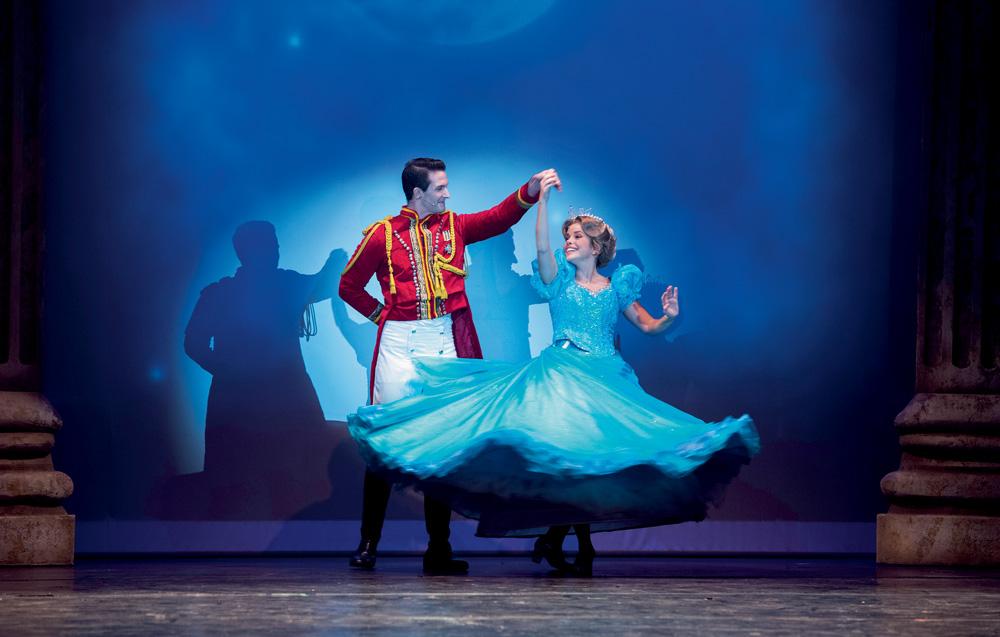 A imagem mostram os dois protagonistas da peça Cinderella. Eles estão dançando, com o príncipe segurando na mão de Cinderella, que está girando em torno de si mesma.