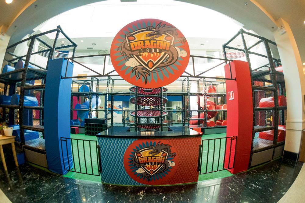 Dentro de um shopping, uma estrutura colorida em vermelho e azul com tobogãs. Na entrada, a placa