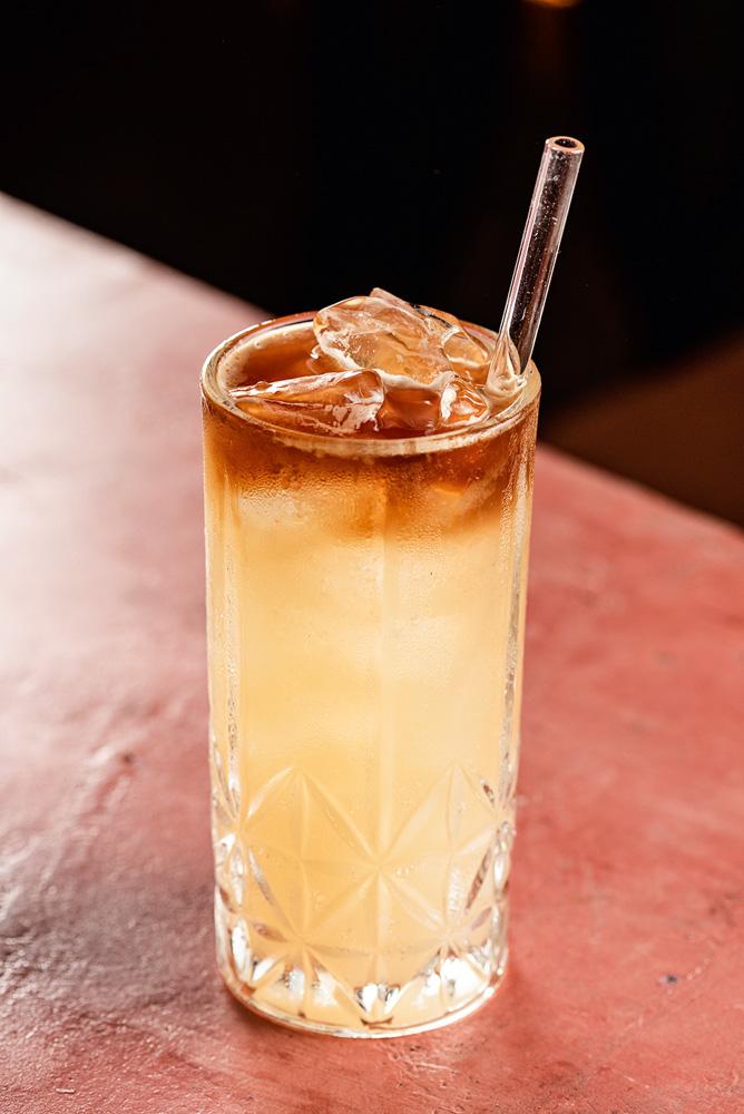 Drinque servido em um longo copo de vidro junto de um canudo, também feito de vidro