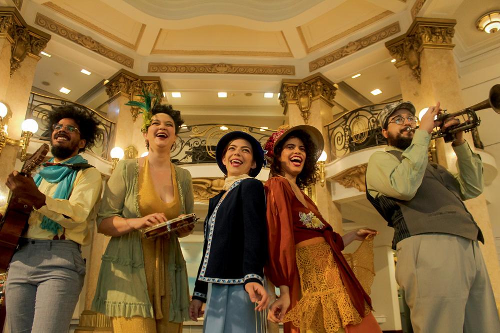 Três mulheres e dois homens, vestindo roupas do século XIX - vestidos e chapéus -, cantam. Ao fundo, dá para ver o prédio do CCBB