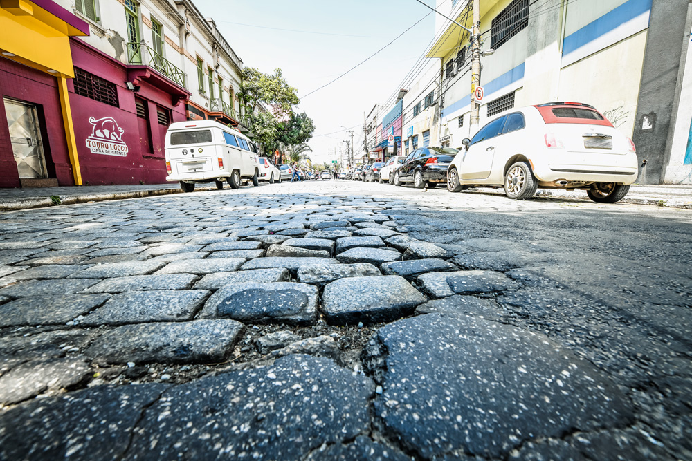 A imagem mostra uma foto bem próxima de um asfalto de paralelepípedos. No centro, há um buraco na rua.