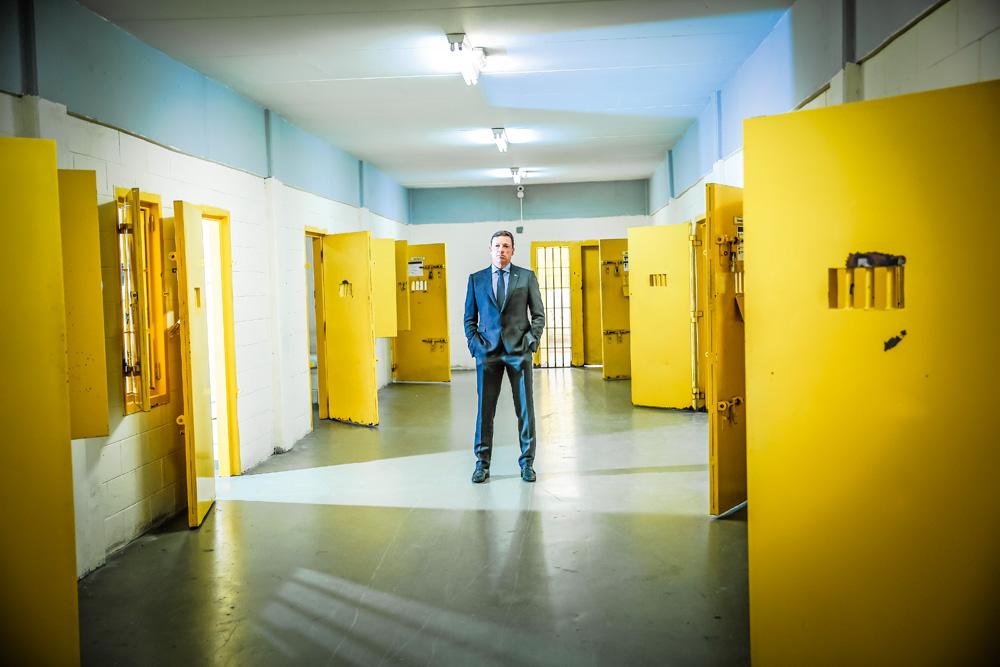 A imagem mostra Fernando José da Costa de pé, em um corredor de celas da Fundação Casa, de terno e olhando sério para a câmera.