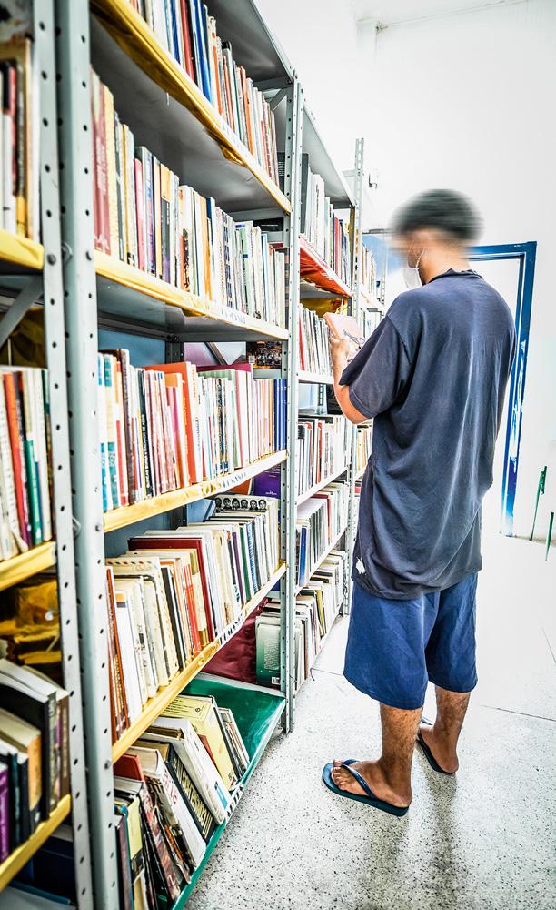 A imagem mostra um jovem tirando um livro de uma estante. Ele está vendo a capa do objeto.