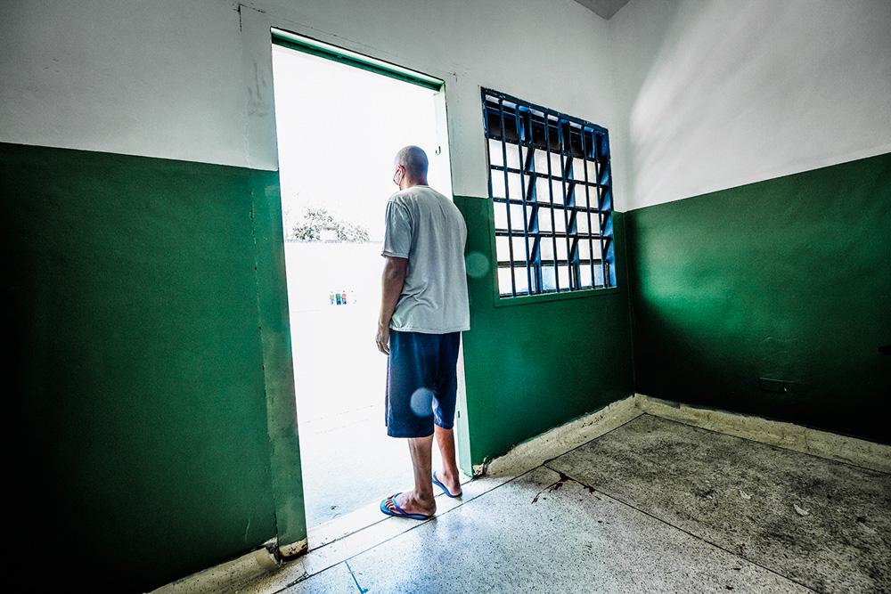 A imagem mostra um detendo, apoiado em uma porta que dá à um ambiente externo, com a luz do sol bem forte.