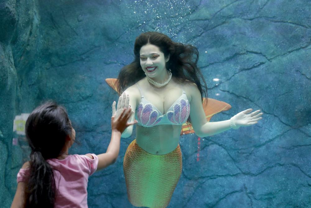 Uma mulher interpretando uma sereia em um tanque de água acena e sorri para uma criança que está do lado de fora do tanque