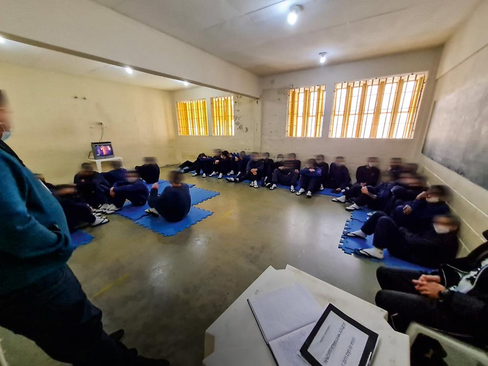 A imagem mostra jovens sentados em tatames em volta de uma televisão pequena.
