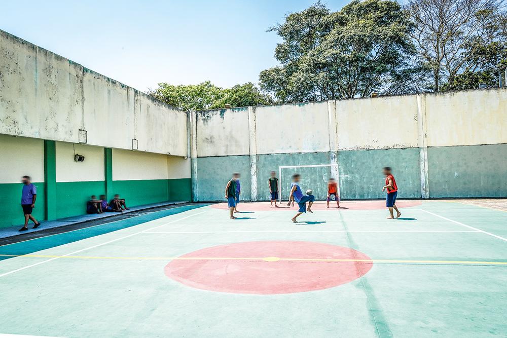 A imagem mostra jovens jogando futsal em uma quadra dentro da Fundação Casa.