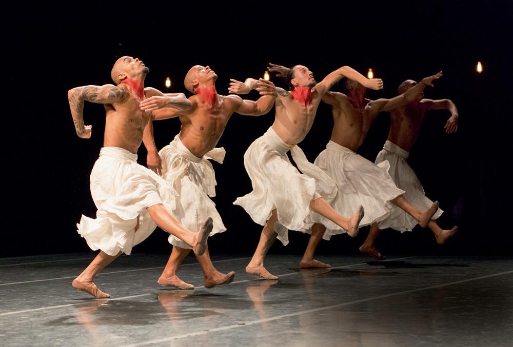 A foto mostra cinco homens sem camisa, com uma grande saia branca e os pescoços marcados com tinta vermelha. Ele estão com os braços abertos e olhando para cima em cima do palco, durante a peça.