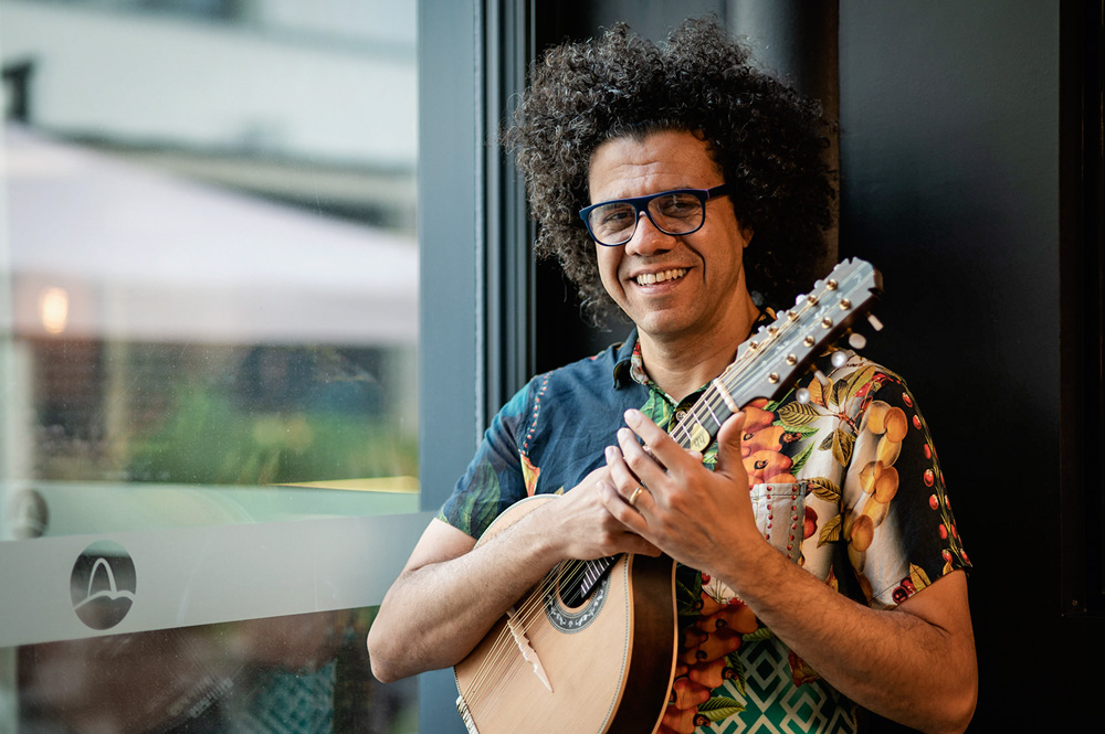 A imagem mostra Hamilton sorrindo, segurando seu instrumento, apoiado em uma janela.