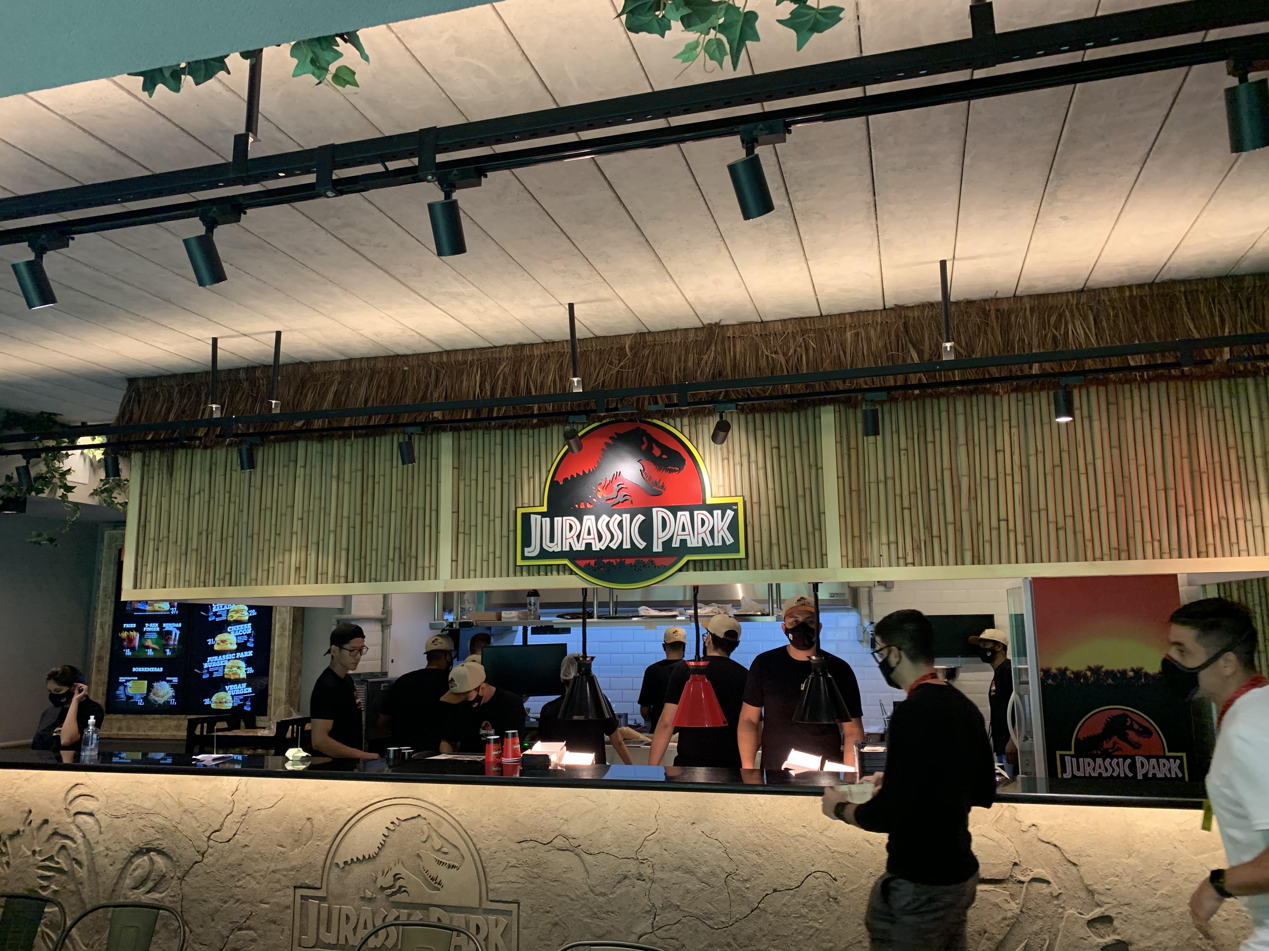 Cozinha da lanchonete Jurassic Park Burger Restaurant aberta para o público. Com balcão de cimento com dinossauro desenhado e teto de bambu.
