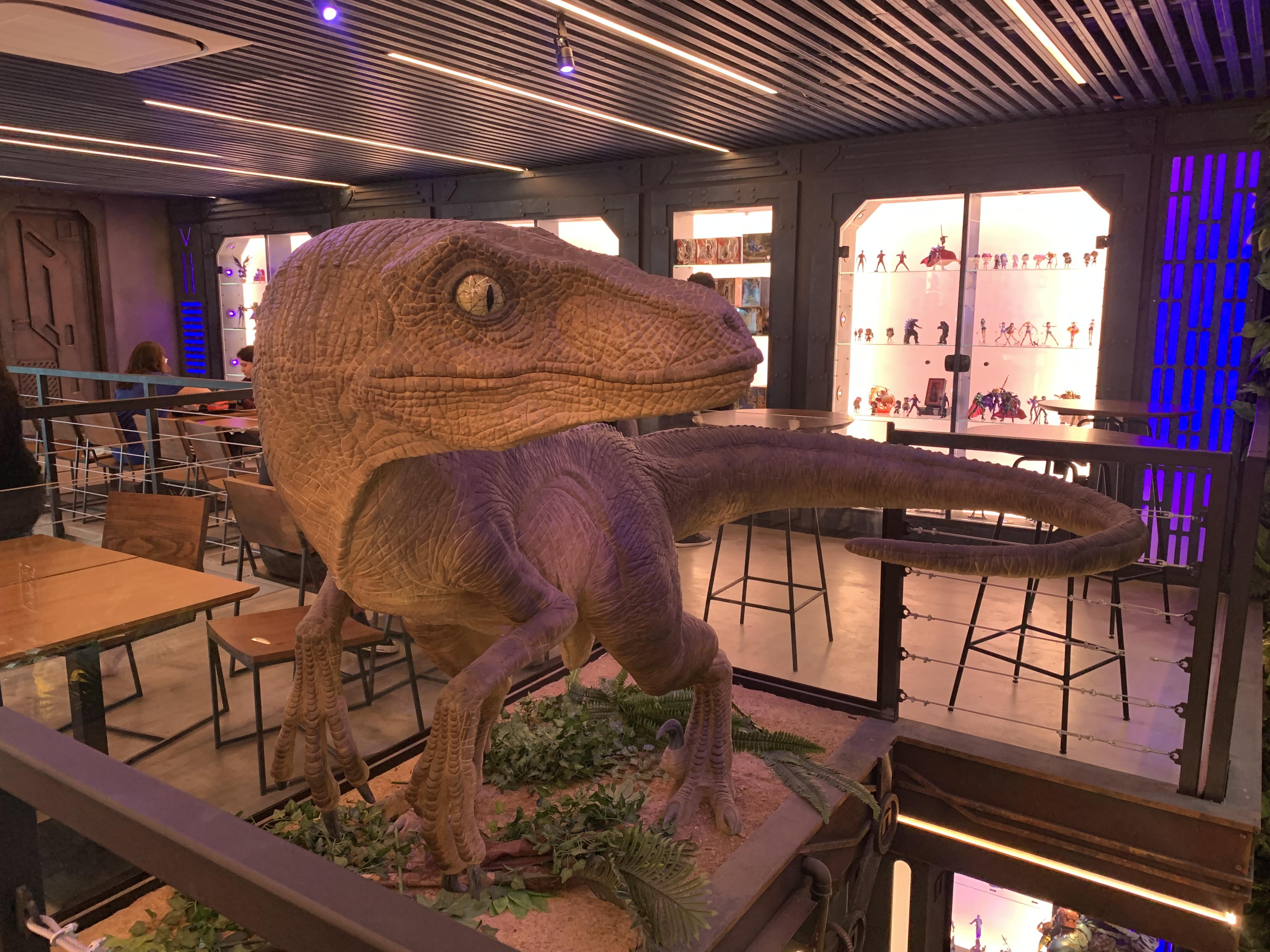 Réplica de um velociraptor olhando para o lado sobre suporte.